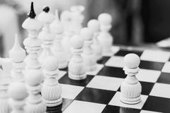 The white piece is a pawn on a wooden chessboard. Black and white photo of chess.