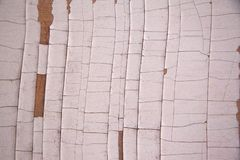 White piece of wood with cracked and chipped paint. For a background or texture or overlay royalty free stock photography