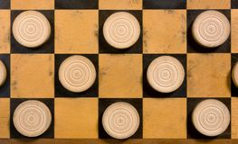 White Pieces on a Checkerboard. A few wooden white pieces on a checkerboard Stock Photos