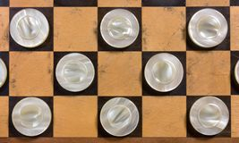 White Pieces on a Checkerboard. A few wooden pearly white pieces on a checkerboard Royalty Free Stock Images