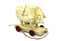 White pig on a white background. Wooden toys, pig, white with red wheels on white background Stock Photography