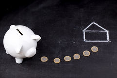 White piggy bank on blackboard: saving for a house Stock Images