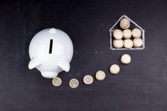 White piggy bank on blackboard: saving for a house Stock Photos