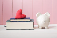 White Piggy Bank Beside Books with Red Heart Cushion. Conceptual White Ceramic Piggy Bank Standing Beside Textbooks with Red Heart Cushion on Top Against Wooden stock images