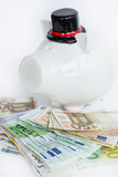 White piggy bank with bowler hat with money on a white background Stock Photography