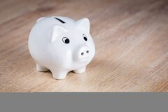 White Piggy Bank on Brown Wooden Surface Royalty Free Stock Images