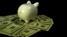 Piggy bank and dollar bills turn on a black background stock video footage