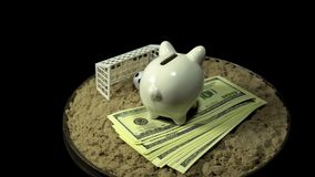 A white piggy bank and dollar bills spins on a black background. A piggy bank stands on a pack of dollars in the sand in front of a miniature football ball stock footage