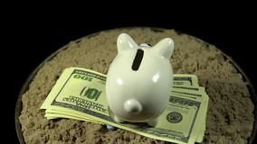 A white piggy bank and dollar bills spins on a black background. Someone puts small heart in the coin box. A piggy bank stands on a pack of dollars in the sand stock video
