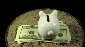 A white piggy bank and dollar bills spins on a black background. A white piggy bank stands on a pack of dollars in the sand in front of a miniature football stock video