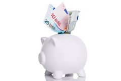 White piggy bank with Euros in the slot Royalty Free Stock Image