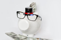 White piggy bank with eyeglasses  with money on a white background Royalty Free Stock Photography