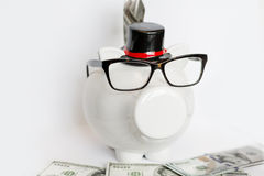 White piggy bank with eyeglasses  with money on a white background Royalty Free Stock Photos