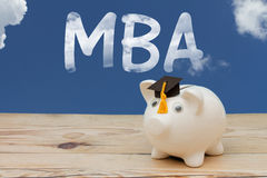 A white piggy bank with grad cap on weathered wood with sky back Stock Images