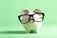 White piggy bank on a green background. White piggy bank with glasses on a muted green background Royalty Free Stock Photos