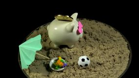 A white piggy bank stands on a sandy beach and spins on a black background. A white piggy bank with hearts stands in the sand next to a umbrella miniature stock video footage