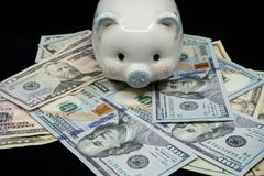 White piggy bank isolated close-up on a pile of United States currency against a black background. Wealth and savings concept. royalty free stock photos