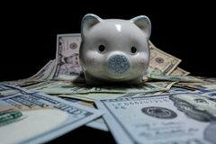 White piggy bank isolated close-up on a pile of United States currency against a black background. Wealth and savings concept. stock image