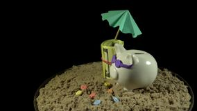 A white piggy bank stands on a sandy beach and revolves on a black background. A white piggy bank in lilac sunglasses stands in the sand next to the folded one stock footage