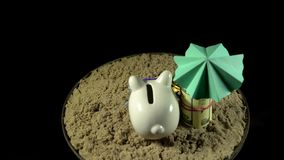 A white piggy bank stands on a sandy beach and revolves on a black background. A white piggy bank in lilac sunglasses stands in the sand next to the folded one stock video