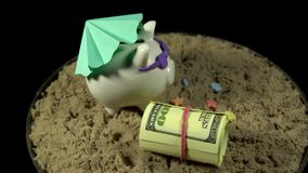 A white piggy bank stands on a sandy beach and revolves on a black background. A white piggy bank in lilac sunglasses under a green umbrella stands in the sand stock video