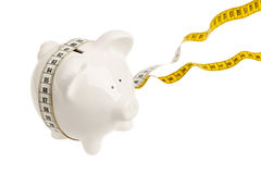White piggy bank with measuring tape Royalty Free Stock Image