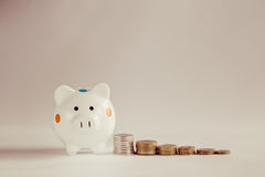 White piggy bank or money box with money coins. Royalty Free Stock Images