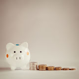White piggy bank or money box with money coins. White piggy bank or money box with money coins Stock Photo