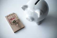 White piggy bank and mousetrap Royalty Free Stock Image