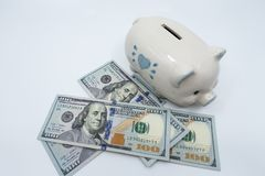 White piggy bank on a pile of United States currency against a white background. royalty free stock photo