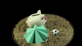 A white piggy bank stands on a sandy beach and spins on a black background. A white piggy bank with pink hearts stands in the sand next to a green umbrella stock footage