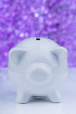 White piggy bank on purple background Stock Images