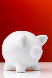 White piggy bank on red background Royalty Free Stock Images