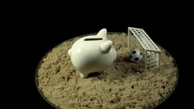 A white piggy bank stands on a sandy beach and spins on a black background. A white piggy bank stands sand in front of a miniature football ball, which is in stock video footage