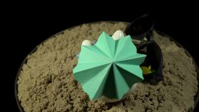 A white piggy bank stands on a sandy beach and revolves on a black background. A white piggy bank in lilac sunglasses under a green umbrella stands in the sand stock video footage