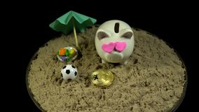 A white piggy bank stands on a sandy beach and revolves on a black background. A white piggy bank with pink hearts and gold bitcoin stands in the sand next to stock footage