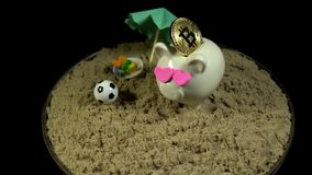 A white piggy bank stands on a sandy beach and revolves on a black background. A white piggy bank with pink hearts and gold bitcoin stands in the sand next to stock video