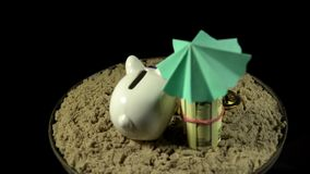 A white piggy bank stands on a sandy beach and spins on a black background. A white piggy bank in lilac sunglasses stands in the sand next to the folded one stock video
