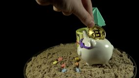 A white piggy bank stands on a sandy beach and spins on a black background. A white piggy bank in sunglasses stands in the sand next to a umbrella, folded with stock video
