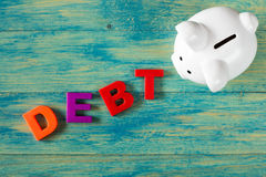 White piggy bank with a word DEBT. Royalty Free Stock Image