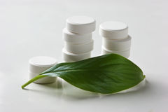 White pill lying on a green leaf Royalty Free Stock Photos