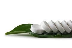 White pill lying on a green leaf Royalty Free Stock Photo
