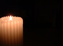 White Pillar Candle. A white ribbed candle on a black background Stock Image