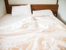 White pillows on the bed and a messy blanket in the bedroom. After waking up in the morning in the hotel Royalty Free Stock Images
