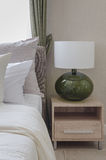 White pillows on bed with modern white lamp on wooden table side Royalty Free Stock Image