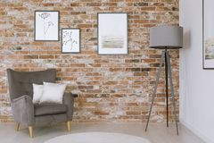 Gallery in classic living room. White pillows on grey armchair and lamp against red brick wall with gallery in classic living room Stock Images