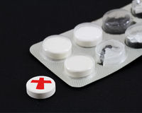 White pills. With red cross in a black background Stock Images