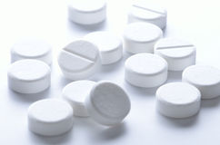 White pills. Close-up of white pills spilled on white background Royalty Free Stock Photography