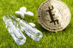 White pills and ampules with bitcoin coin on the grass background - healthcare cost concept Royalty Free Stock Images