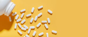 Free White Pills Are Poured From A Jar On A Yellow Background. Food Supplement, Multivitamins, Medications. Stock Photos - 208454333